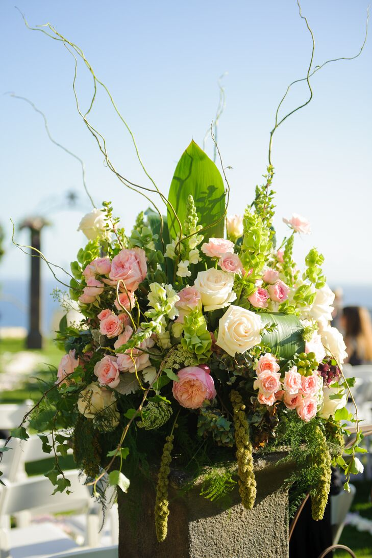 Lush arrangements of greens and blooms decorated the indoor-outdoor spaces at the venue throughout the day. Pink and white roses were arranged with bells of Ireland, stock, branches and leafy greens.