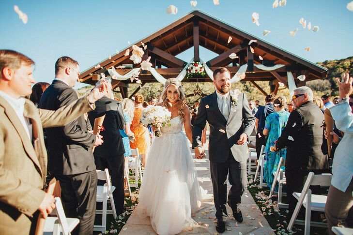 "Courtney and Andrew's guests showered them in flower petals as they walked up the aisle as newlyweds. Andrew picked the upbeat song, James Taylor's live version of ""How Sweet It Is,"" since it coordinated with the rustic, country feel of their outdoor ceremony."