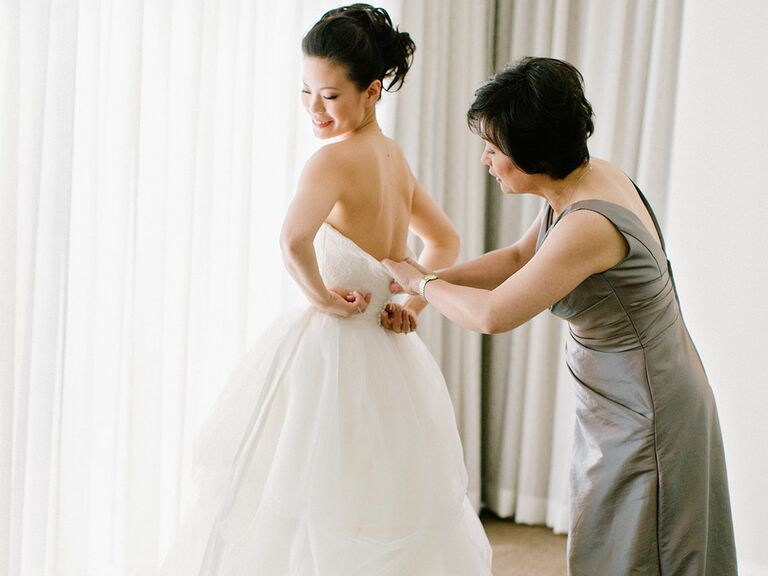 Mother zipping up wedding dress