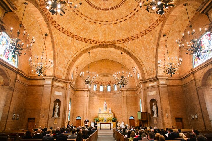 """Amanda and Alex exchanged vows in a Catholic communion service at Basilica Shrine of St. Mary in Wilmington, North Carolina. """"St. Mary's Basilica is absolutely beautiful with its high arches and dome ceiling,"""" Amanda says. """"There wasn't much decor needed."""""""