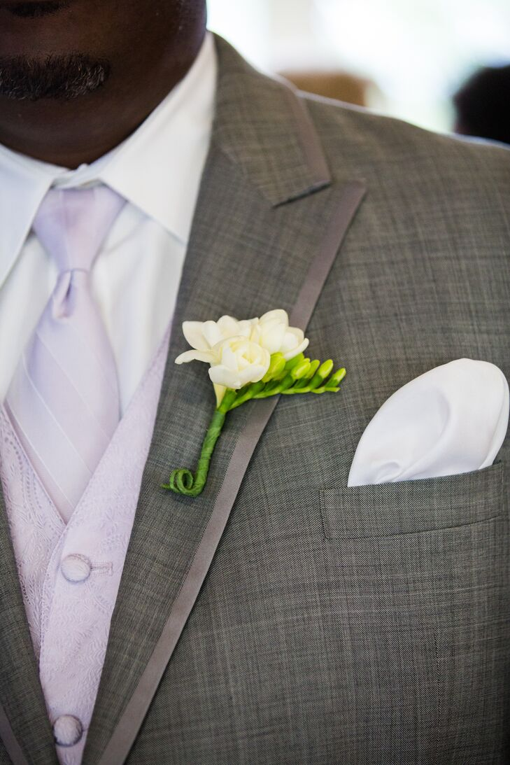 A simple, white rose boutonniere was paired with the groomsmen's gray tuxedos with purple vests and ties.