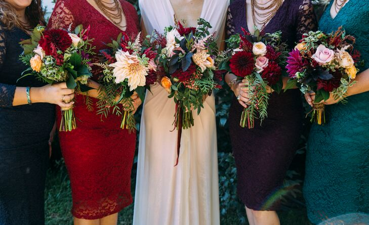 The bridesmaids wore the same lace dresses in shades of deep red, navy, purple, and emerald green which tied in well with their textured bouquets.