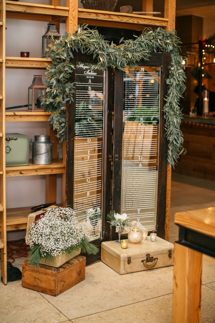 The seating chart was written on the glass of a wooden window frame in white. The frame was decorated with ivy and arranged with vintage trunks and small bouquets of white flower.