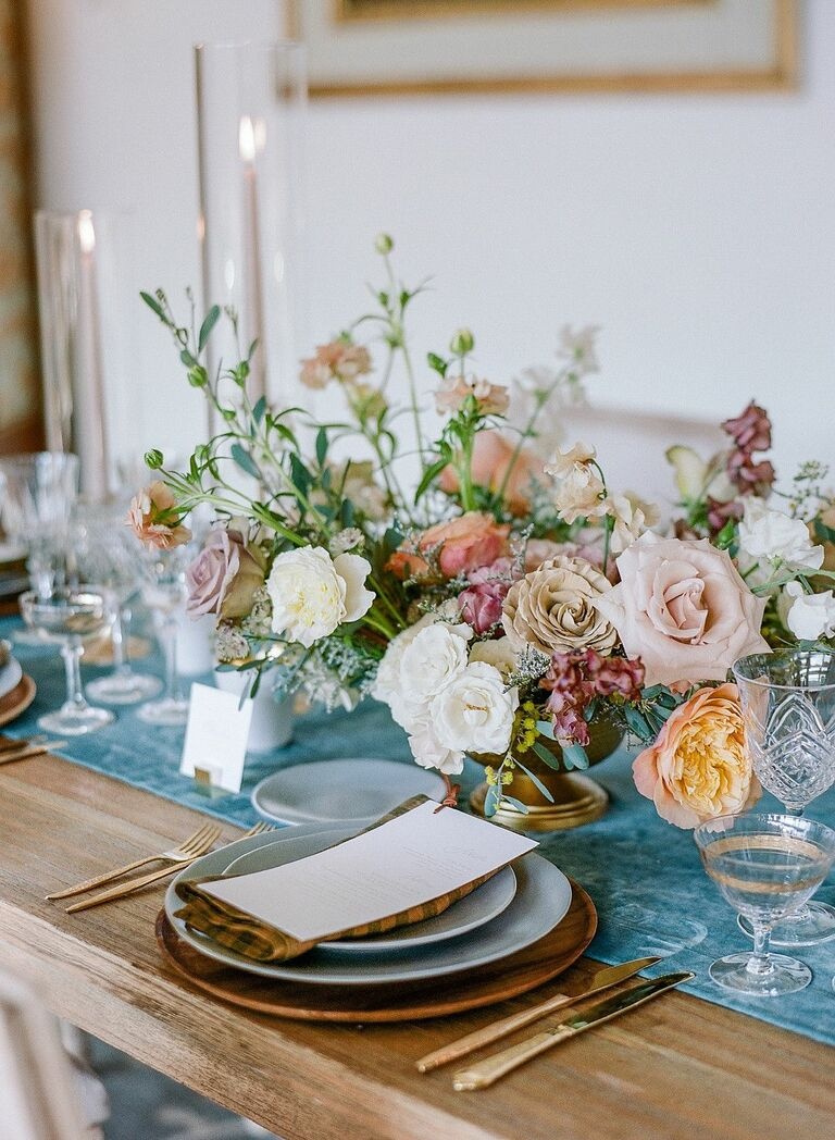 Floral centerpiece on farm table with blue runner