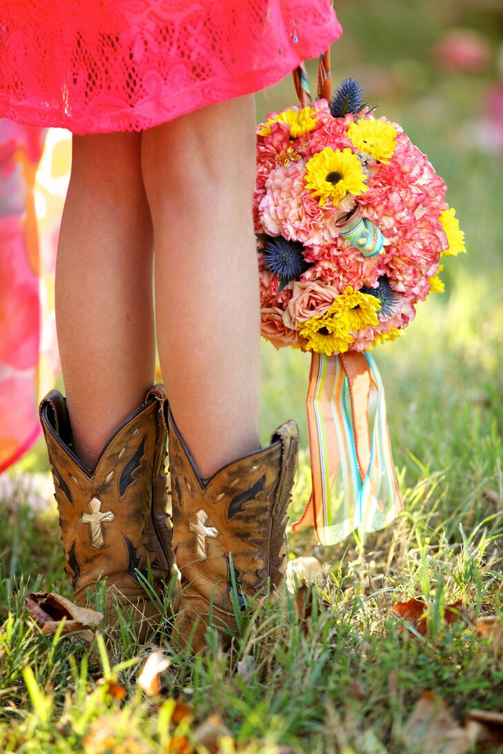 The couple's flower girl, Marshall's niece, wore a hot pink lace dress and cowboy boots. She carried a carnation and daisy pomander with ribbon handles.