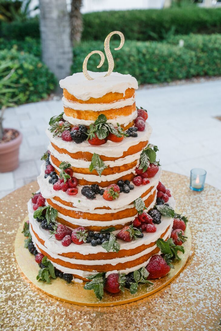 """At first, a naked cake was far from Ashley and Phil's minds, but they loved how it came out. With some help from the bakers at Publix, they served a four-tier confection covered in raspberries, blueberries, blackberries and strawberries between layers of white buttercream frosting. Complete with a rhinestone """"S"""" topper and gold sequin tablecloth, they let the dessert serve as a focal point for their reception."""