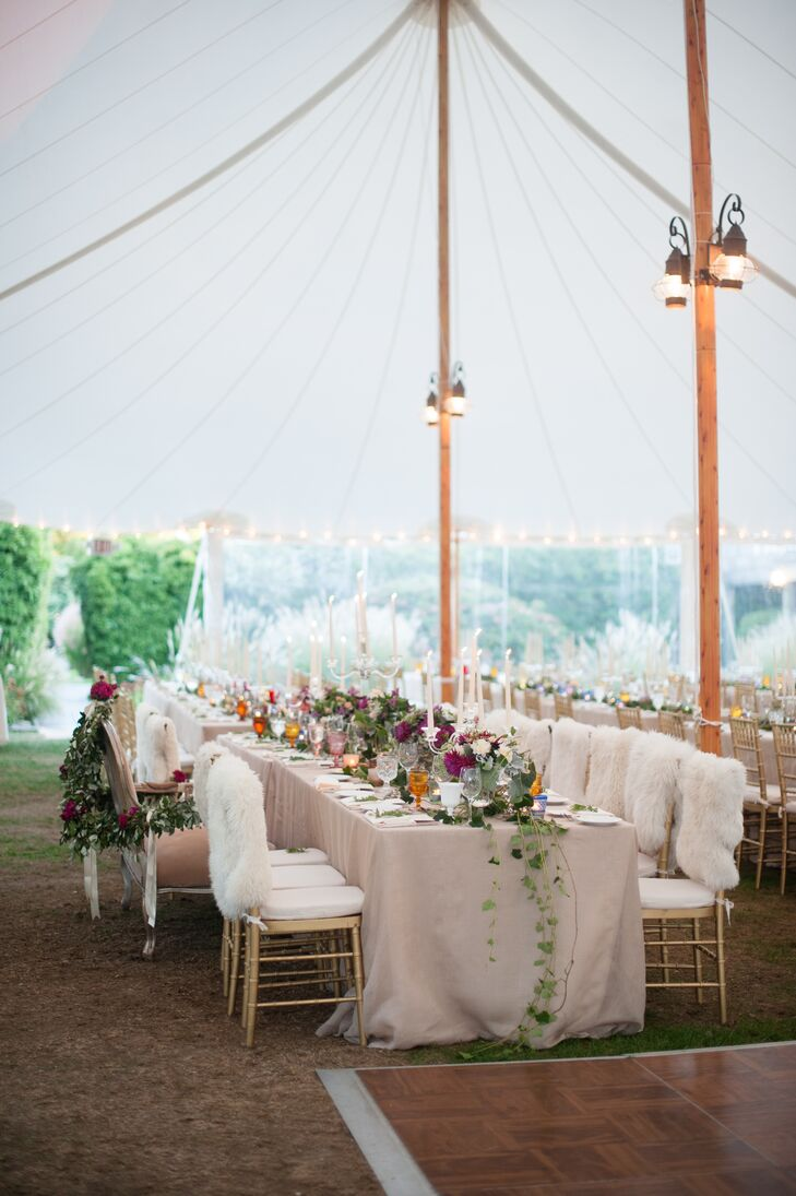 After exchanging vows, the newlyweds and their guests headed to the open-air tent for the reception. Warm candlelight and twinkling strands of bistro lights filled the space with ambiance, while arrangements of richly hued blooms and ivy with a wild quality injected a note of romance into the decor.