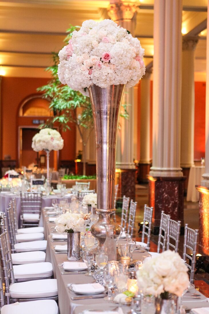 One of the Landmark Center's most noteworthy features is the 20ft ceiling. While most of the centerpieces dotting the reception tables were small, Sadie's Couture Floral & Event Styling created two tall arrangements of hydrangeas and roses in silvery trumpet vases for each table to work with venue's impressive height.
