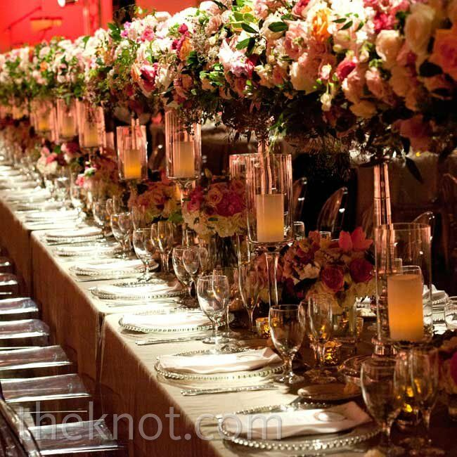 The 48-foot-long head table was topped with super-lush arrangements of varying heights, pillar candles and mercury-glass votives.