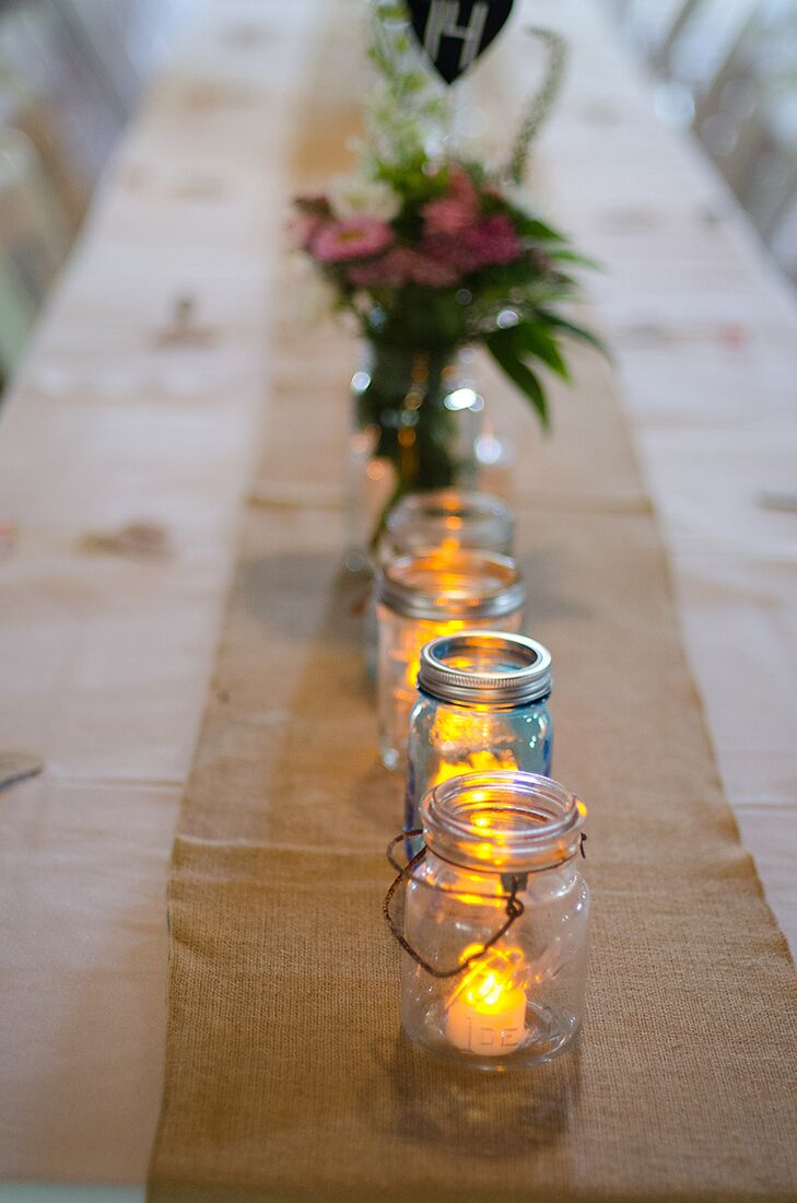 Keeping with the rustic style of the wedding, Mary and Sam's dining tables featured long, burlap table runners with mason jars filled with battery-powered candles.