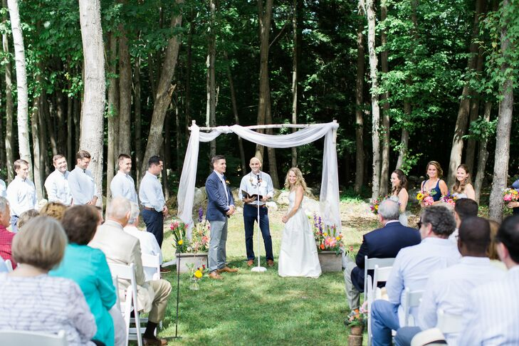 "The ceremony took place at the forest's edge, with Liz and Boris and their guests gathering under the shade of tall old-growth trees. Bundles of bright flowers and a quaint white birch wedding arch framed Liz and Boris as they said their ""I dos,"" with a panel of ethereal white fabric overhead, giving the setting a note of whimsy."