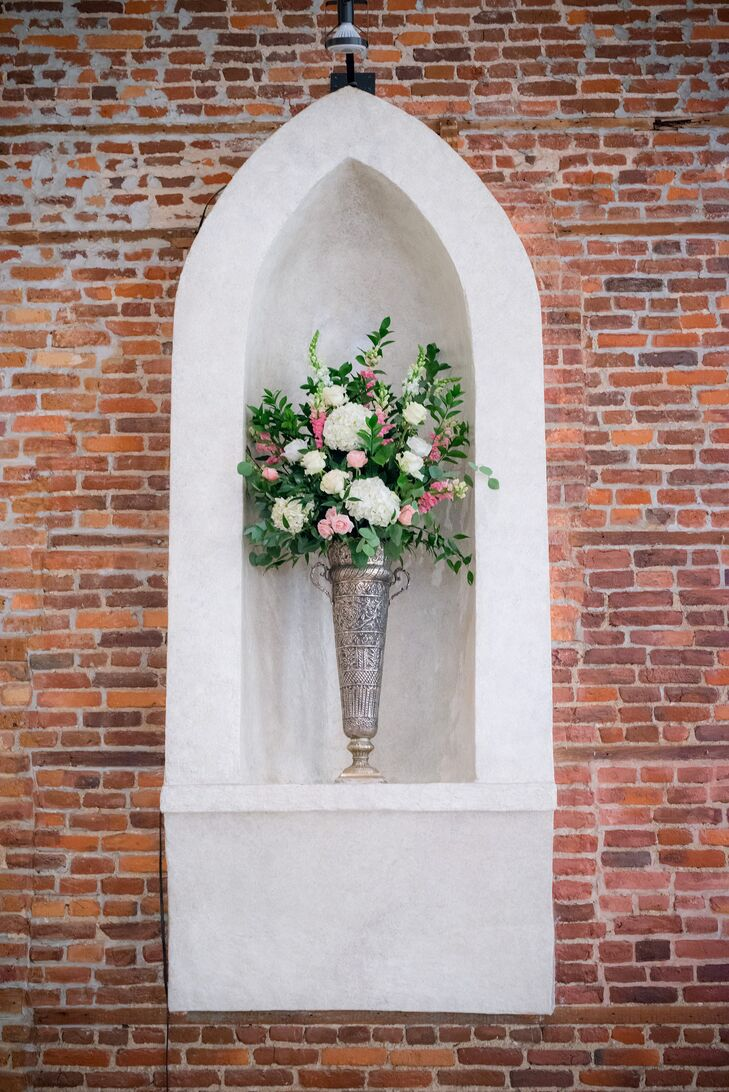 Elizabeth and Tim filled the old Catholic Church venue with ornate silver urns filled with white hydrangeas, pink roses and plenty of leafy greenery.