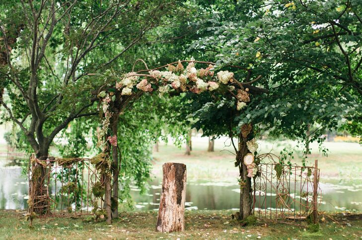The whimsical outdoor ceremony took place at the groom's childhood home in front of a pond. Tree stumps lined the aisle, along with painted sticks and pinecones for a more rustic feel.