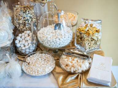 Gold and white colored wedding candy buffet
