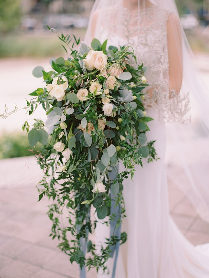 """""""I wanted an organic, timeless bouquet that was reminiscent of yesteryear,"""" Caroline says. She carried a dreamy cascade of jasmine vine, eucalyptus, roses and dusty miller."""