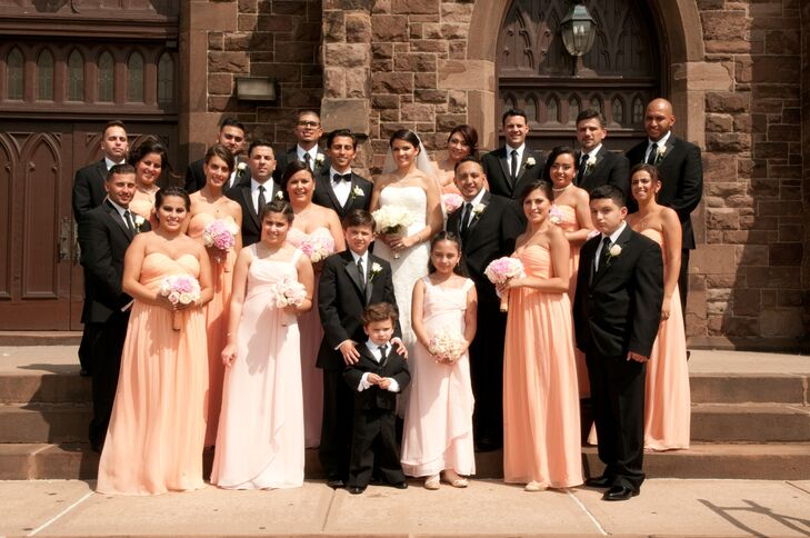 The groomsmen wore classic black suits while the bridesmaids wore long peach dresses.