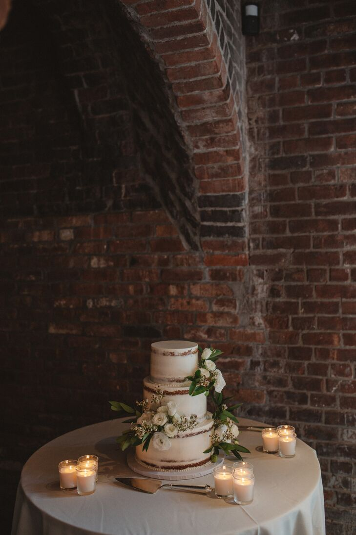 Sugar Lane Cake Shop of Nesconset, New York, created Nancy and Michael's three-tier, roughly frosted white cake with white ranunculus.