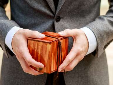 hands holding a ring box