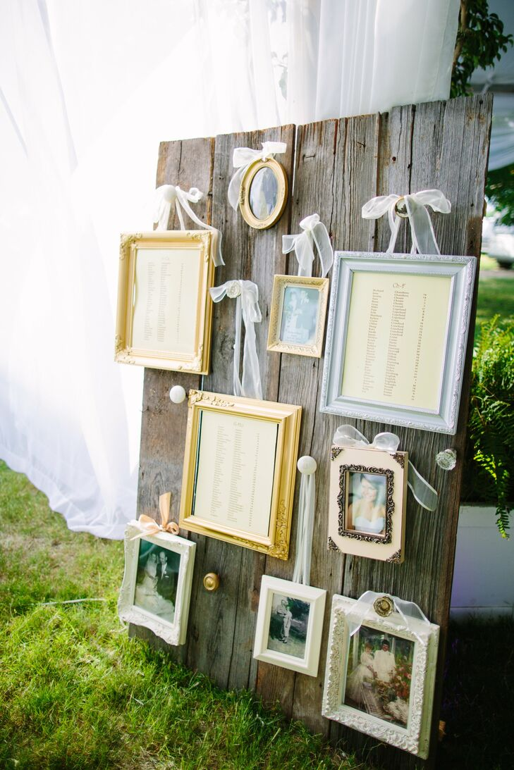 Framed seating charts along with wedding photos of the couple's great grandparents, grandparents and parents hung on the vintage barn doors in the reception tent.