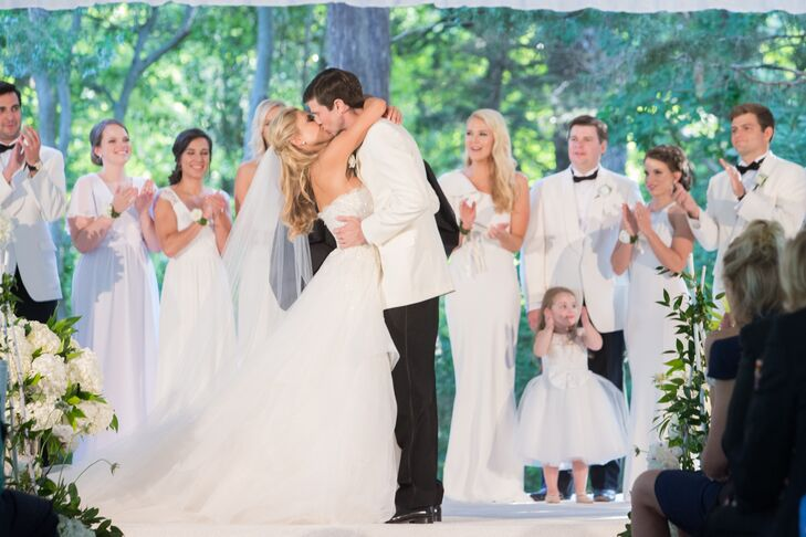 Wedding Party Celebrating Couple's First Kiss at Ceremony