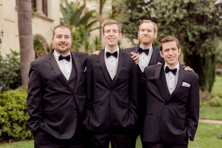 David and his groomsmen each wore a sharp, black tuxedo with a white shirt and black bow tie. Each groomsmen wore a boutonniere of a single ivory rose and carried an engraved pocket watch that the groom had ordered from Etsy as a gift.