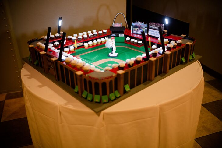 """Mark's dad spent months constructing a mini replica of Busch Stadium in St.Louis, Missouri. The stadium is home to the St. Louis Cardinals, Mark's favorite baseball team. """"The stadium was incredible and huge,"""" Shelby says. """"The stands were filled with mini cupcakes that looked like a little crowd. On the pitcher's mound stood a custom model of us that pictured Mark holding me in his arms, both wearing Cardinals jerseys with CAIN on the back and 20 on one jersey with 14 on the other. The figurine looked exactly like us! Our names and wedding date were also on the scoreboard."""""""