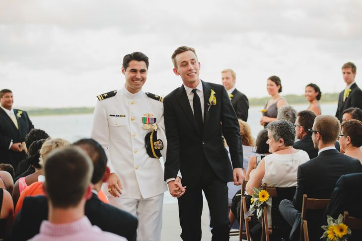 "Michael wore his Full Dress Whites uniform and Joey wore a sleek J.Crew suit with Cole Haan shoes. ""Because of the venue and waterfront background, we didn't need a lot of decor for the ceremony,"" says Joey. ""We went with elegant yellow floral arrangements for our aisle markers and let the Charleston Harbor and Ravenel Bridge take care of the rest!"""