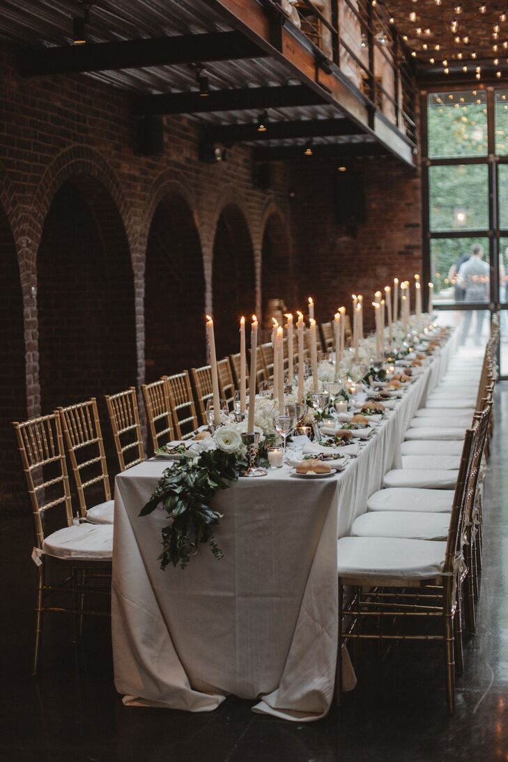 At the reception, long banquet tables were topped with crisp white linens, a long lemon-leaf and eucalyptus garland, and tall white candles.