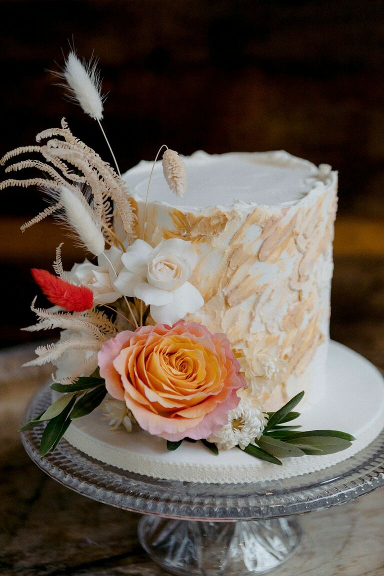 Rustic single-tier wedding cake decorated with dried elements