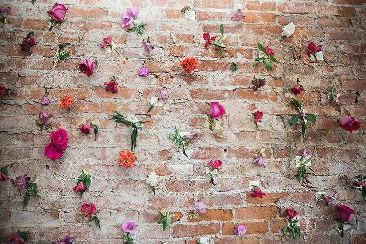 "At the reception, a brick wall was decorated with individual flowers for a fun photo-booth backdrop. ""The visual irony gave an elegant yet organic feel to the celebration,"" Andi says."