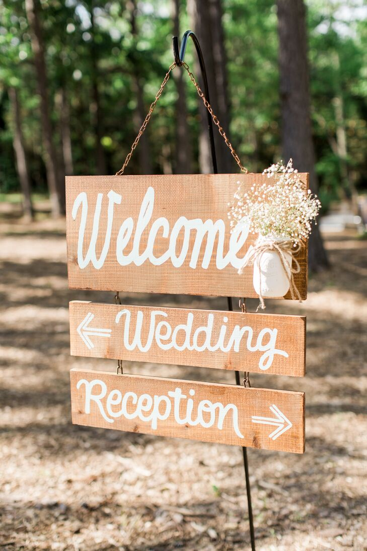 A wooden welcome sign adorned with baby's breath greeted guests upon their arrival.