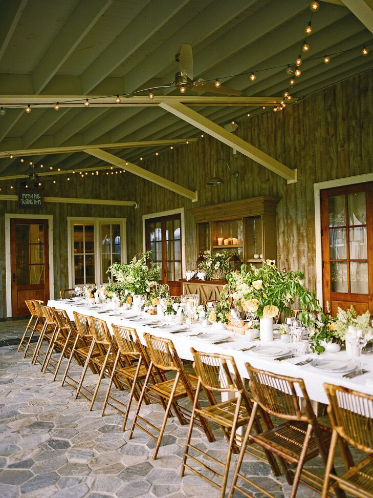 A guest list of 80 meant the couple could seat everyone at a single 80-foot wooden table on the veranda of Pippin Hill's Tasting Room. Bistro lights glowed above the whitewash table topped with white linens, trays of peaches and centerpieces of garden roses, green viburnum berries and herbs.