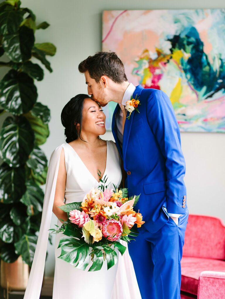 Groom kissing bride holding colorful bouquet of tropical flowers