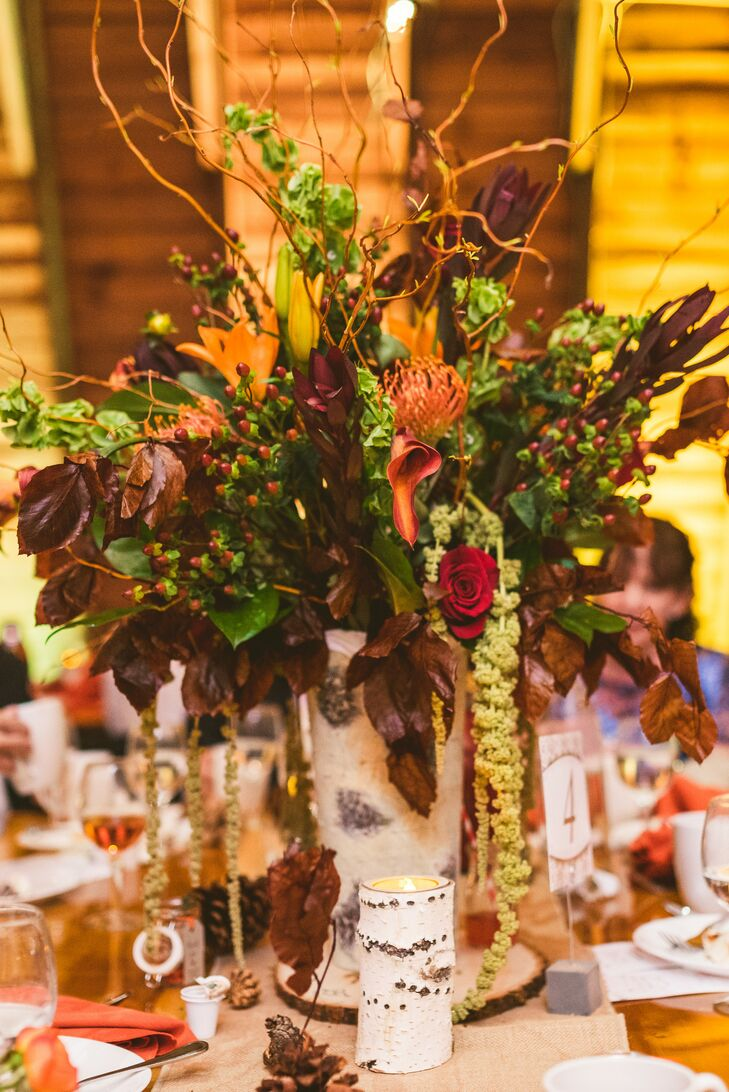 Wooden tables at the reception were paired with one of two centerpieces; the tallest versions took natural to a new level. Birch wood formed the vase while a display of greenery, red hypericum berries, magnolia leaves, mango calla lilies, red roses, curly willow and orange tulips spilled over the sides. Matching birch-wood-accented candles and pinecones also circled the arrangements.