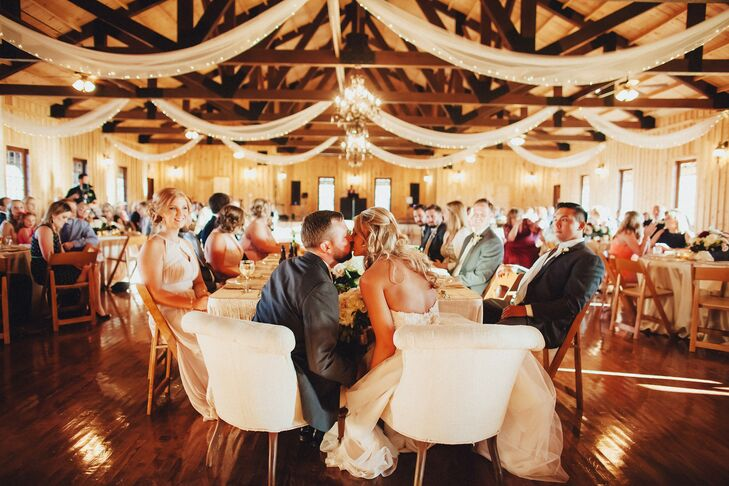 "Courtney and Andrew hosted their reception indoors for the rustic feel of the limestone and wood building at Bella Springs Events in Boerne, Texas. Tulle and string lights hung in the rafters, and a trio of chandeliers added glam to the room. ""It was a great blank canvas for us,"" Courtney says. ""It had the foundation that we wanted and we knew we'd be able to make it our own."""