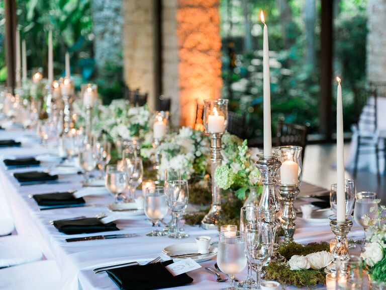 Wedding candles at the reception surrounded by moss