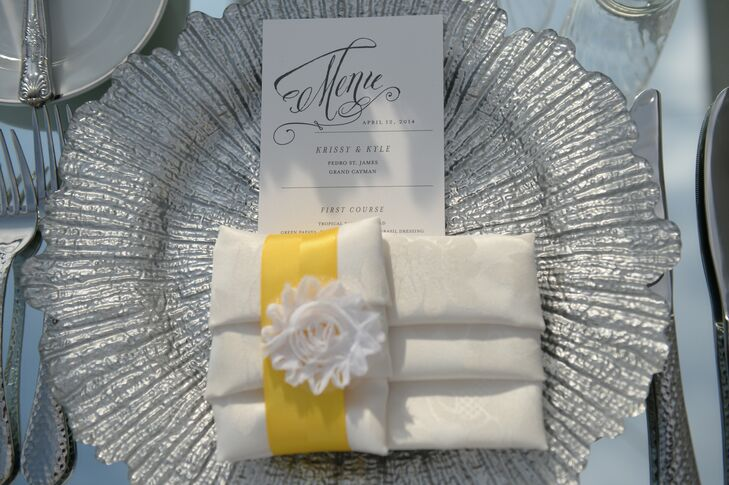 Each guest's place setting consisted of silver chargers,  an elegant menu card and a folded napkin tied with a bright yellow ribbon that matched the bridesmaids bouquets.