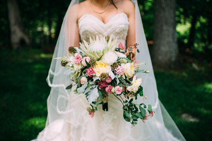 """Kim's bouquet resembled a garden in itself. Pink and fuchsia roses, dusty miller, scabiosa, seeded eucalyptus and white ranunculus all cascaded down the arrangement. Ibranyi Is Floral marked the top with a grand white king protea, yellow roses, yellow astilbes and orange gloriosa lilies. Even seeded eucalyptus and white veronica popped from the arrangement. But what made it especially personal was the wrap. """"I had three of my grandmother's brooches attached to the stems. Wrapped around that was my godmother's wedding handkerchief. I call her 'fairy godmother,' """" Kim says."""
