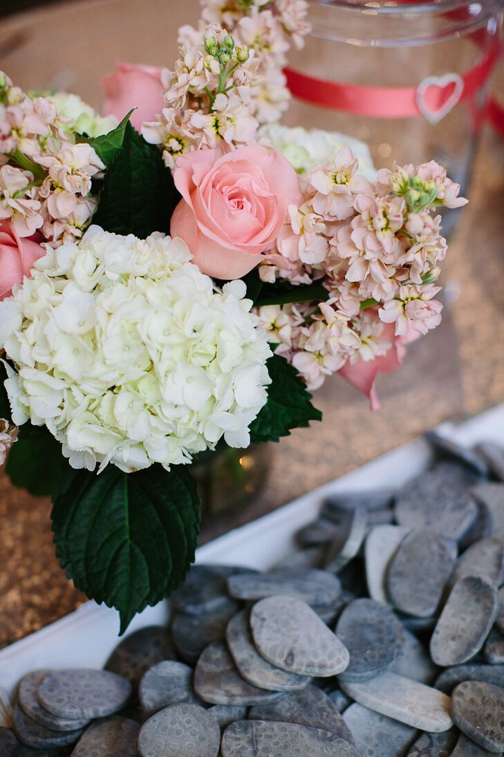 The floral arrangements were created by Monarch Garden and Floral Design. The couple's accents included white hydrangeas and coral roses.