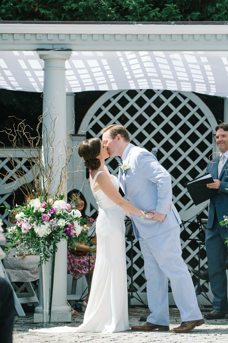Allison and Alistair were married outdoors under a white pergola at the New York Botanical Garden in the Bronx, New York. Beside the altar area, tall arrangements of white hydrangeas, purple roses and branches added height and texture to the space.