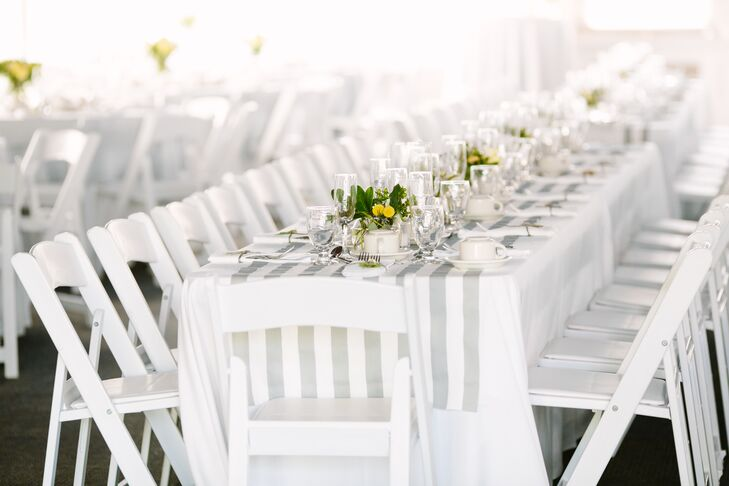 """When it came to the decor, Lynn and Joe went for a fresh, clean and summery aesthetic. """"Having worked at the golf course, I'd seen so many weddings that just felt overdone to me,"""" says Lynn. The pair worked with a soft color palette of white and gray, adding a touch of cheerfulness through subtle pops of yellow and green. They lined the long banquet tables with crisp white linens and gray striped runners for a contemporary feel, with votive candles and understated arrangements of hydrangeas and craspedia infusing the space with warmth."""