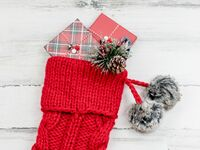 red knit christmas stocking with wrapped gifts