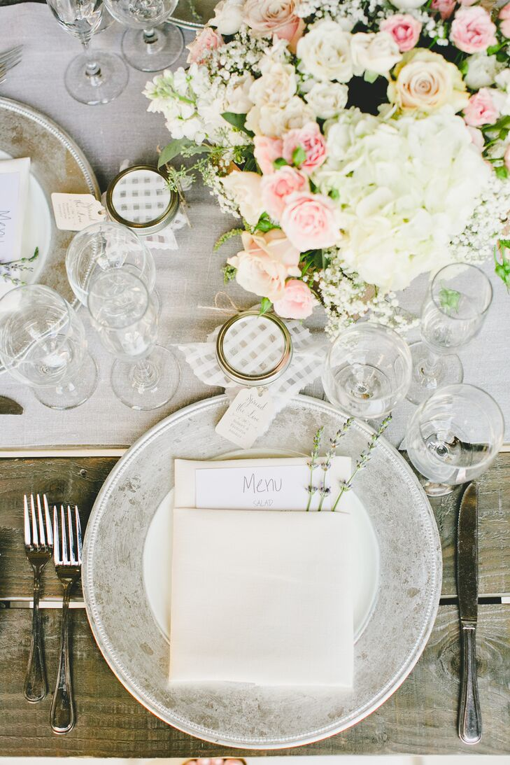 The ivory napkins folded at each seat contained a white and gray menu card inside its flaps, with lavender sprigs poking out. The arrangement rested on top of white and gray vintage dinnerware, where each guest sat and enjoyed their meal.