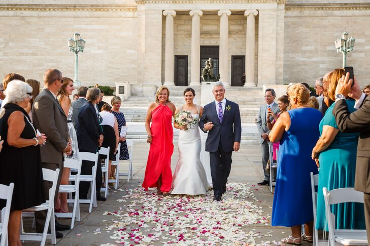 Jackie walked arm in arm with her parents down the aisle toward the front, where Bryan awaited her arrival for the ceremony. Since the architecture of the museum surrounded the space, little decor beyond the rose-covered aisle had to be added.