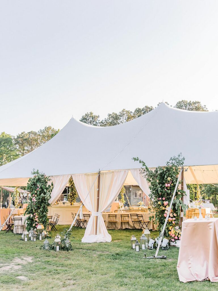 Outdoor tent at garden-themed wedding with gauzy white drapes