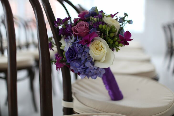 Andrea carried a bright and seasonal bouquet of mixed flowers including hydrangeas and roses in jewel tones like deep purples and pinks.