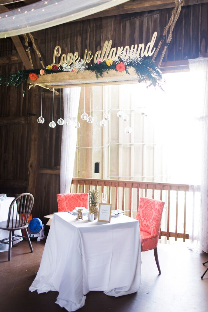 "A large, handmade planter that read ""love is all around"" hung high above the couple's sweetheart table. ""My mom and stepfather made it using flowers and floating candles,"" Molly says. ""It really added a wow factor, since you noticed it when you walked into the barn."""