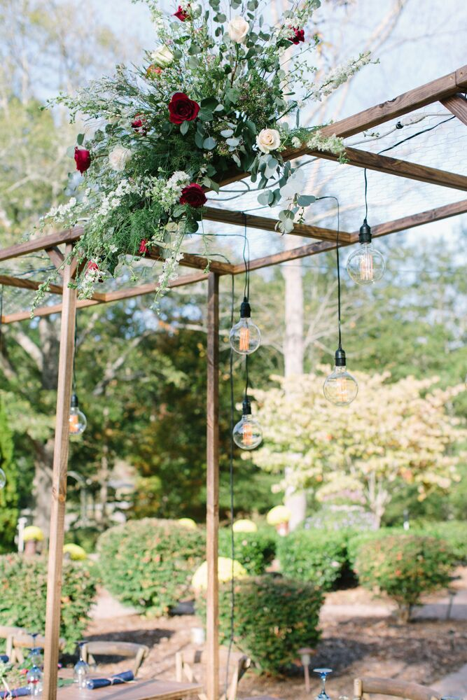 Above the bridal party's reception table was an awning made of wood and chicken wire topped with an arrangement of greens and white and red roses. Strings of bulbs hung from the wire.