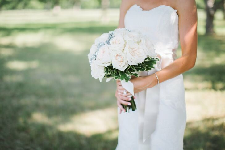 """A band of rhinestone brooches ran through the middle of Kayla's bouquet of pink and ivory garden roses. """"It was a different approach to the brooch design—a way to incorporate the trend but not outshine the beautiful roses!"""" she says."""