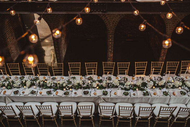 Long banquet tables were topped with crisp white linens, a lemon-leaf and eucalyptus garland, and tall white candles.